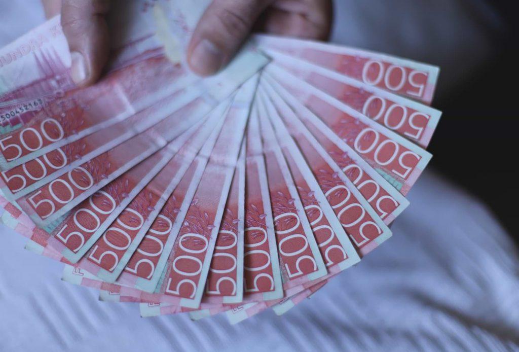 Man visar upp förskott på lönen i 500-sedlar