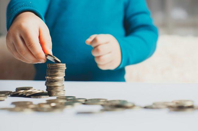 Barn i blå tröja som räknar mynt