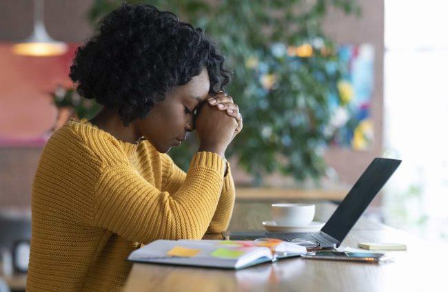 Kvinna vid dator som är orolig för sin ekonomi