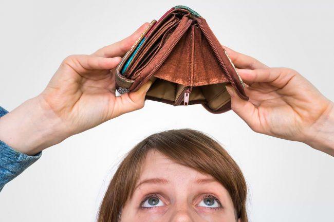 Kvinna med tom plånbok över huvudet